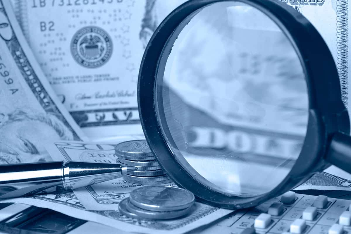 Magnifying glass in front of money, money laundering
